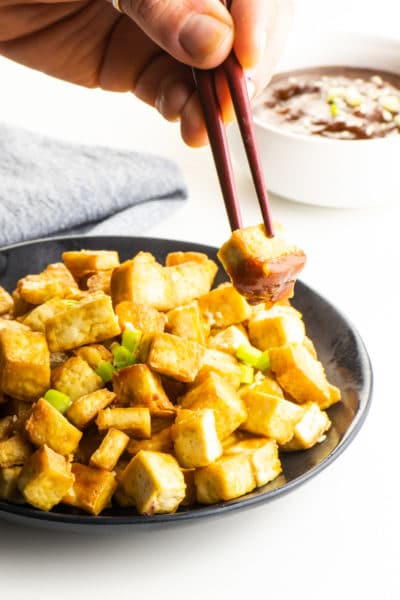 A hand holds chopsticks with a piece of air fryer tofu in it with dipping sauce on it. The full plate of tofu is behind it.