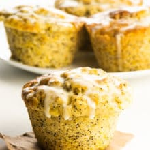 A vegan orange poppyseed muffin on a piece of brown pepper with more muffins behind it.