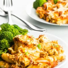 Two plates of meatless baked ziti and steamed broccoli with forks between them.