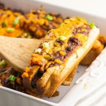 A vegan baked hot dog is held on a spatula over the rest of the casserole dish.