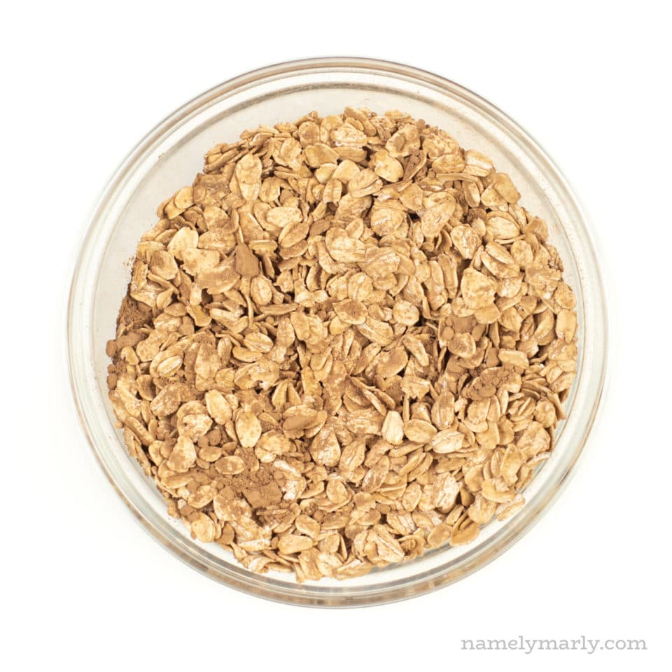 A bowl of oats mixed with cocoa powder and other ingredients.