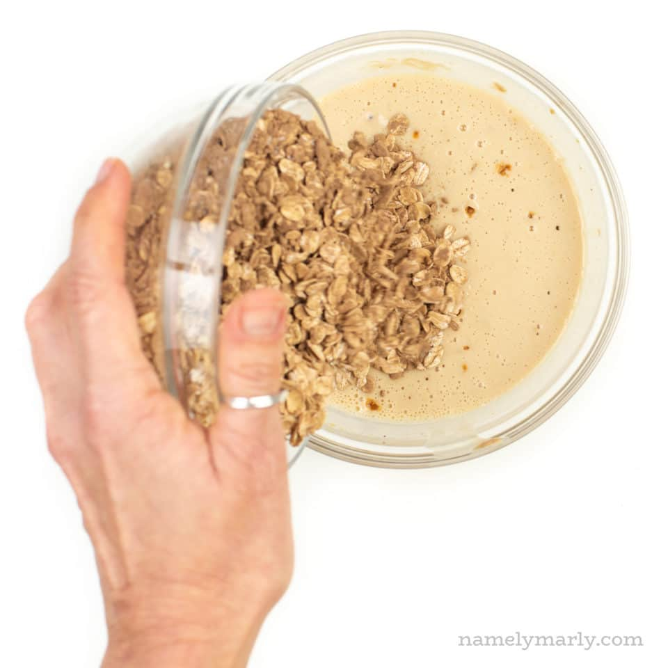 A hand holds a glass bowl and is pouring the contents of oatmeal into a plant-based milk mixture.