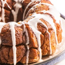A loaf of Vegan Monkey Bread sits on a plate with lots of frosting drizzled over the top.