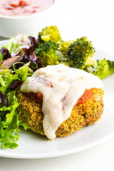 A vegan chicken parmesan patty on a plate beside steamed broccoli and salad.