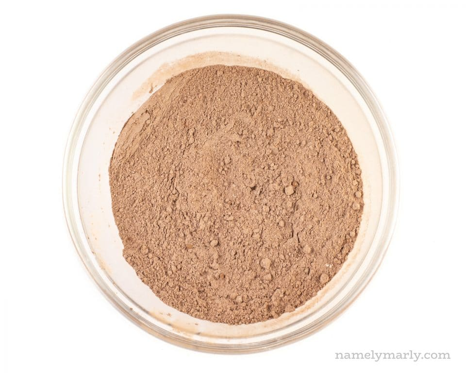 Cocoa powder has been mixed with flour and other dry ingredients and sits in the bottom of a glass mixing bowl.