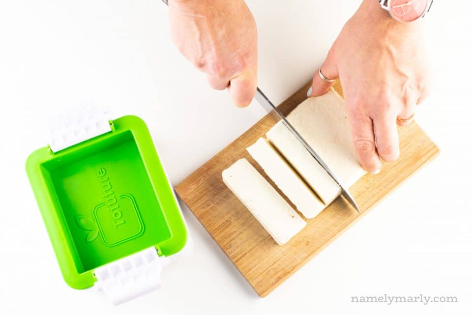 A hand holds a knife and is cutting tofu. It's sitting next to a tofu presser gadget.