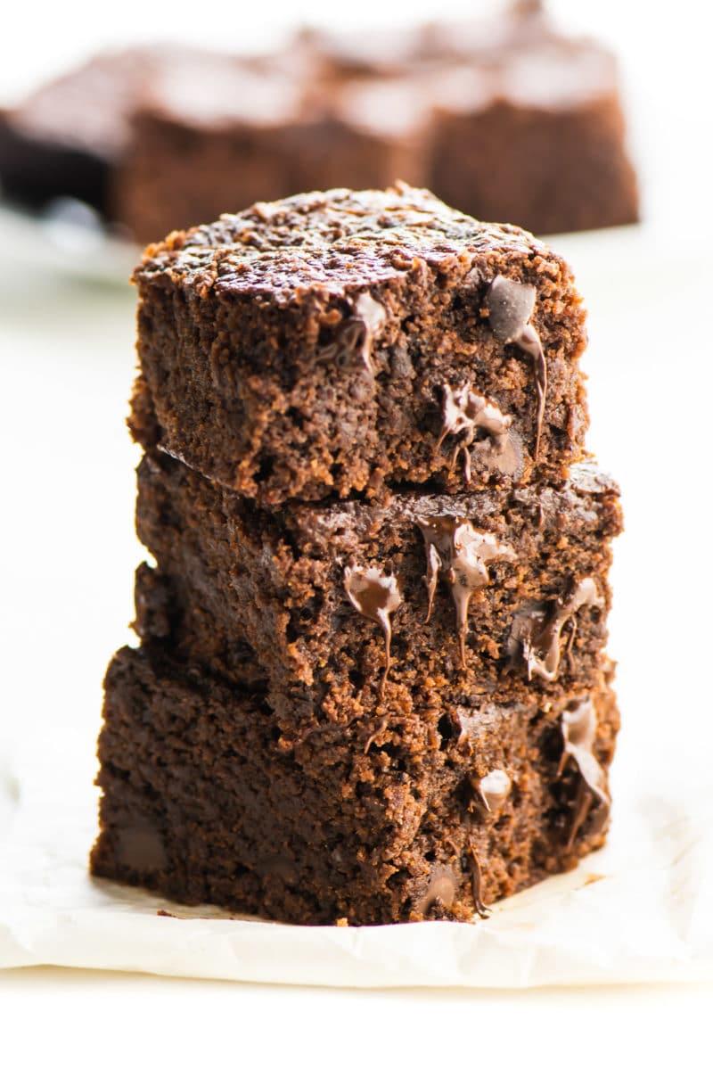 A stack of vegan brownies with several more brownies behind them.
