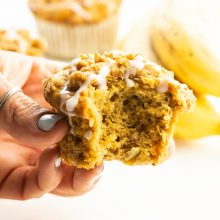 A hand holds a banana muffin with a bite taken out. More muffins and bananas are behind it.