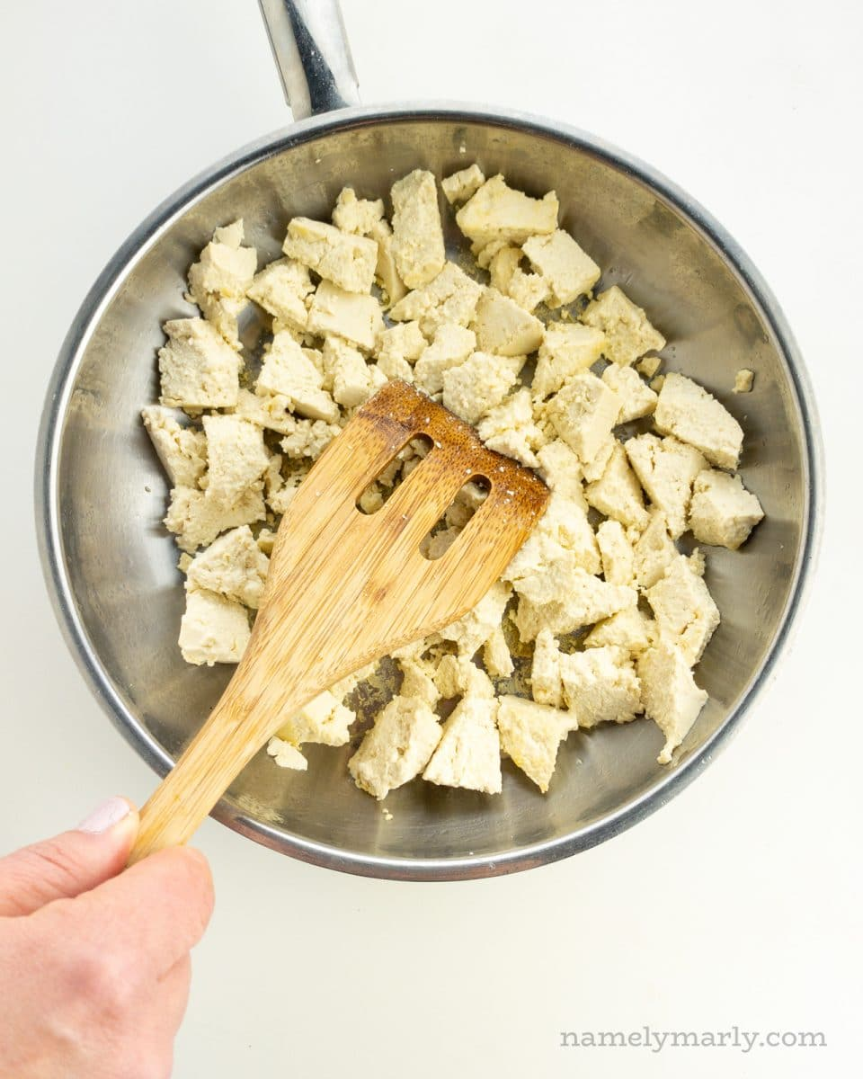 Tofu is in a skillet and a hand holds a spatula breaking the tofu into smaller pieces.