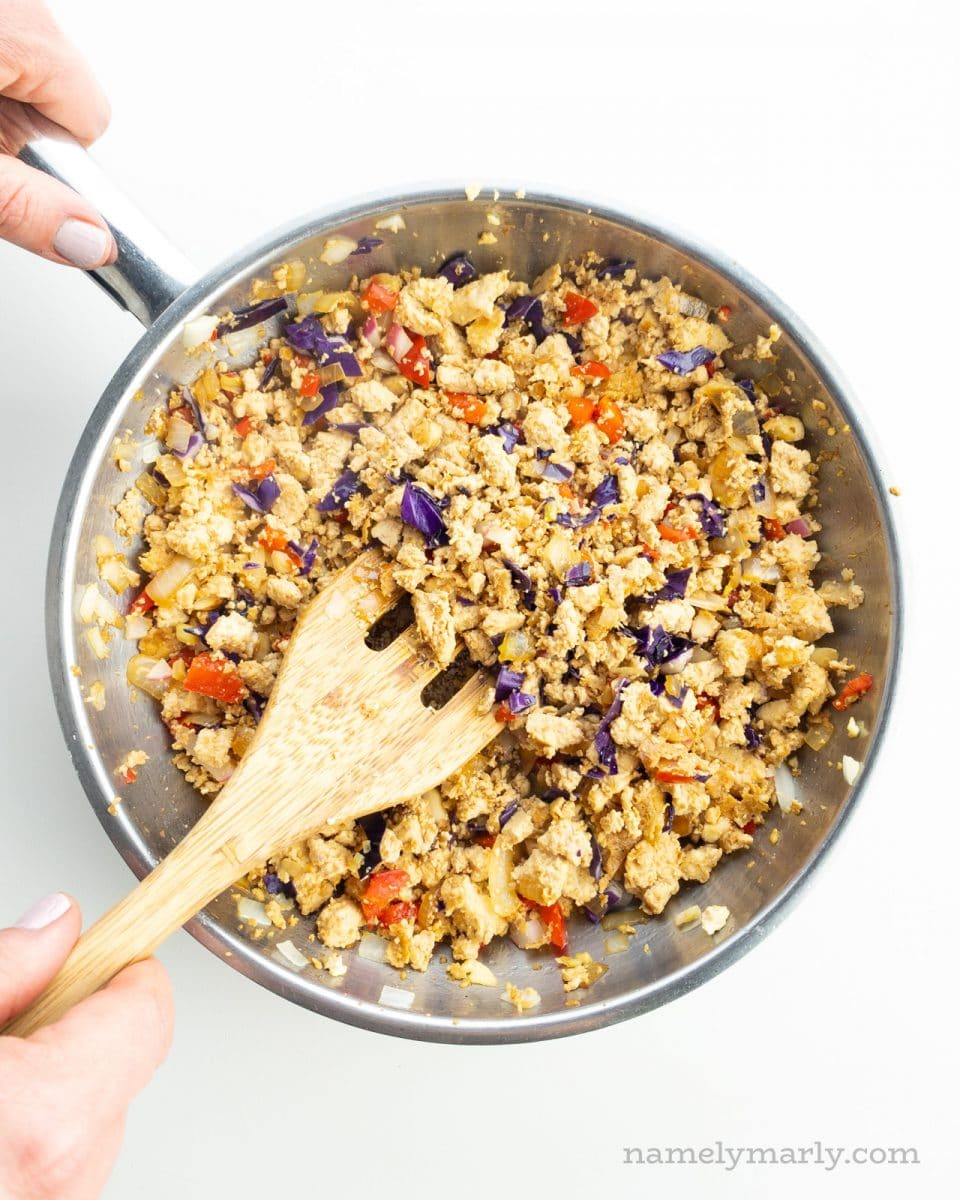 Tofu filling with veggies is in a skillet and a  hand holds a spatula stirring it.