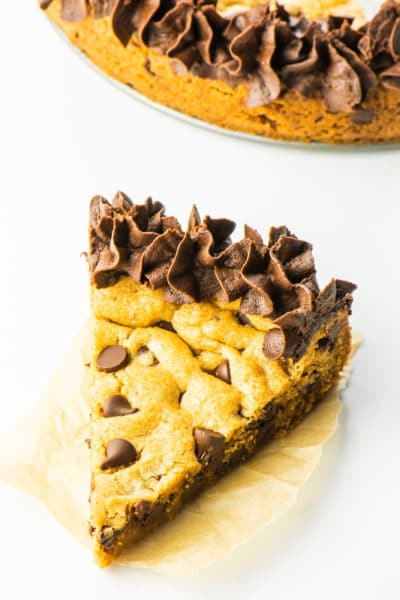 A slice of chocolate chip cookie cake on a napkin sits in front of the rest of the cake.