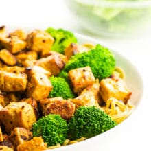 A bowl of cooked tofu with steamed broccoli.