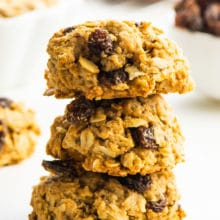 Three oatmeal cookies stacked with more cookies and ingredients around it.