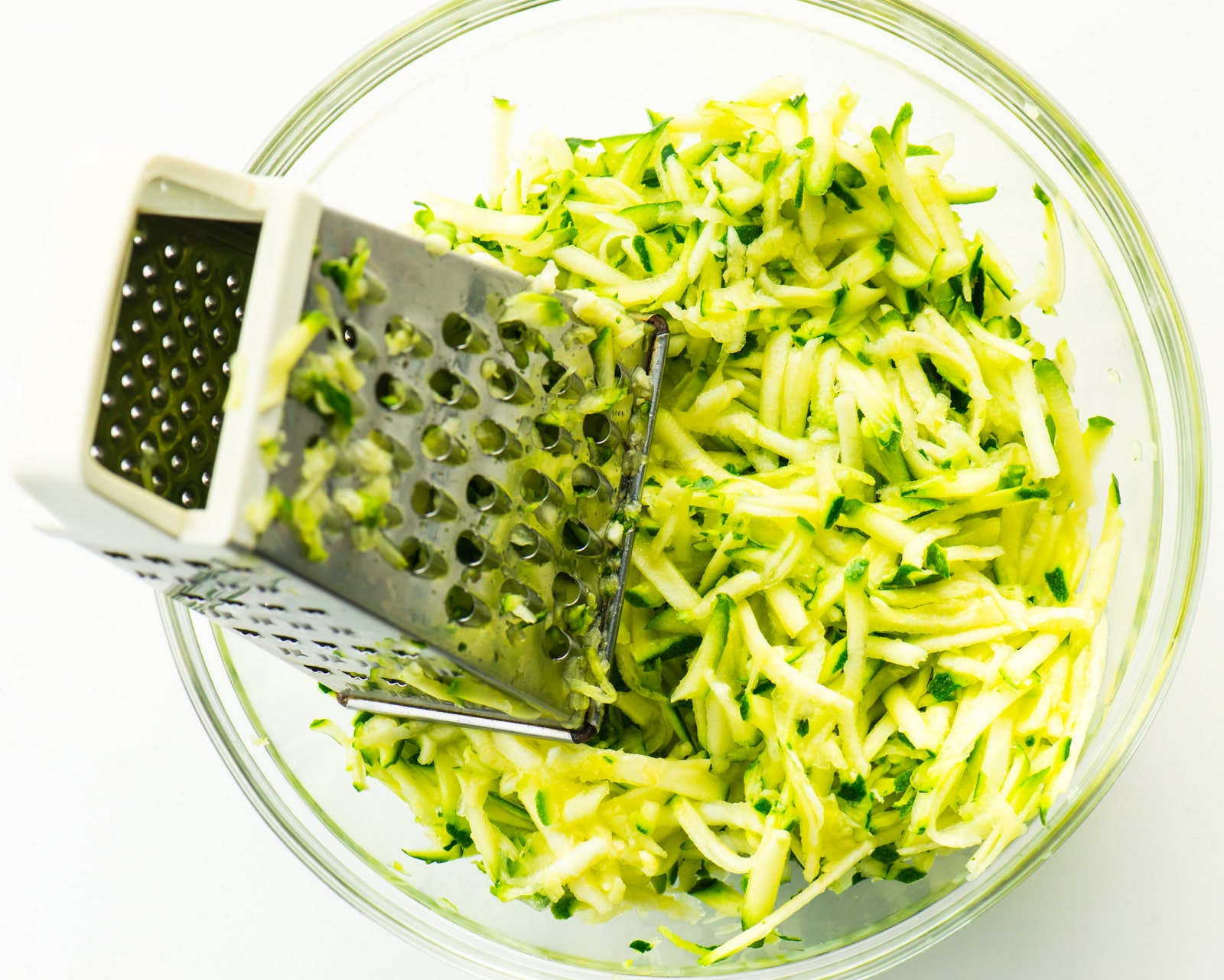 A glass bowl contains shredded zucchini along with a metal shredder.