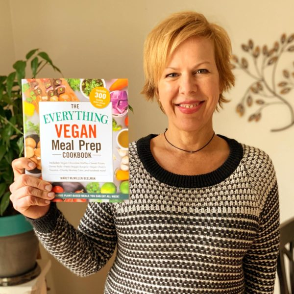 Photo of Marly holding our book, The Everything Guide to Vegan Meal Prep Cookbook