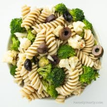 Looking down on a bowl full of pasta salad, showing rotini noodles, broccoli, cauliflower, and black olives.