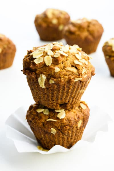 Two applesauce muffins are stacked on top of each other with more muffins behind them.