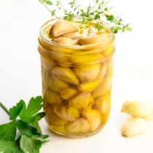 A mason jar holds many cloves of cooked garlic sitting in olive oil. There are cloves are garlic beside it along with green herbs.
