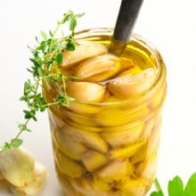 A mason jar holds garlic confit with a spoon. There are green herbs on top of and beside the jar.