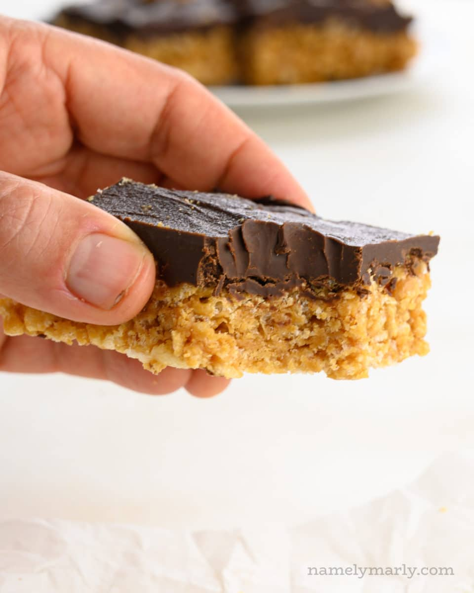 A hand holds a peanut butter rice krispies treat with a bite taken out of it.
