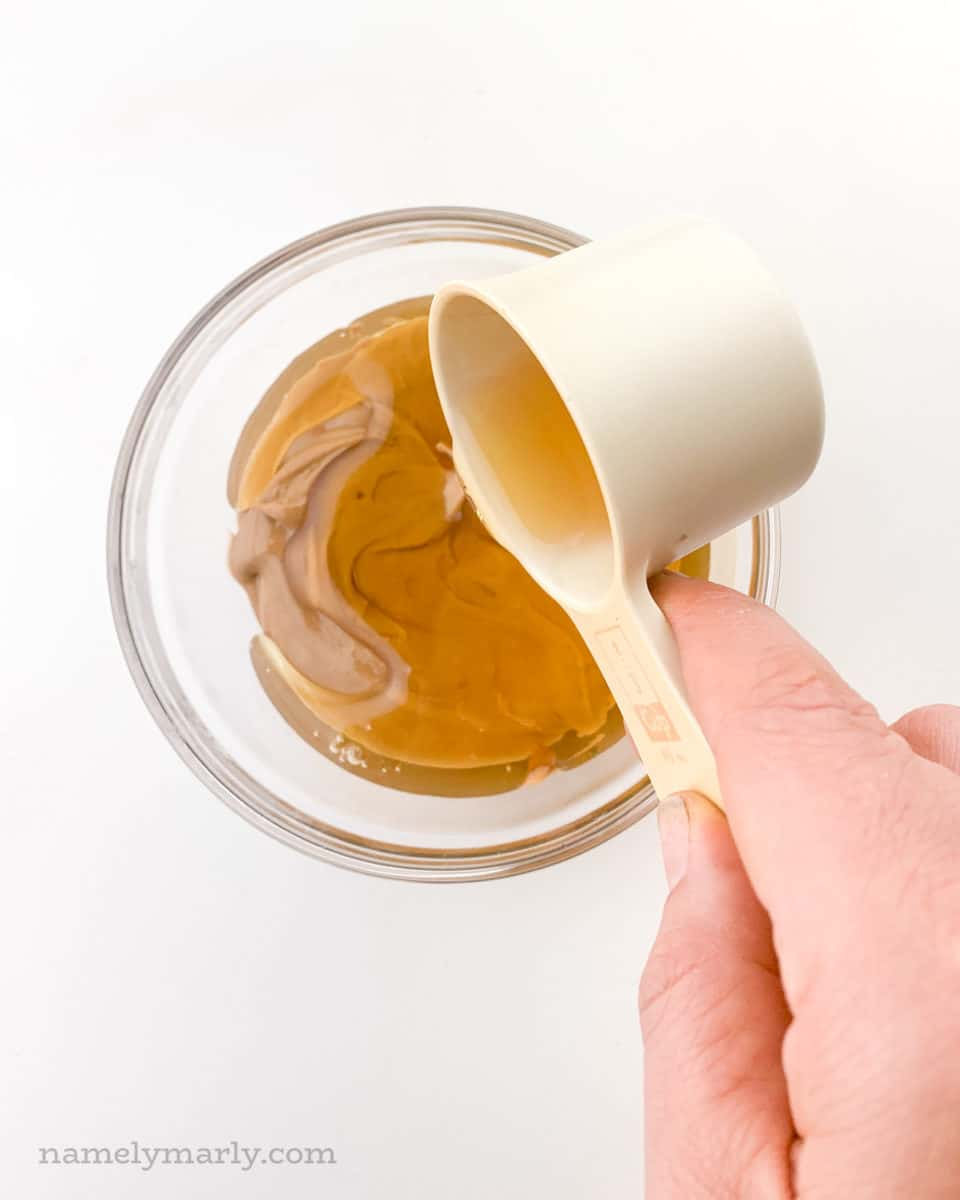 A hand holds a measuring cup full of syrup and is pouring it over a glass bowl full of peanut butter.