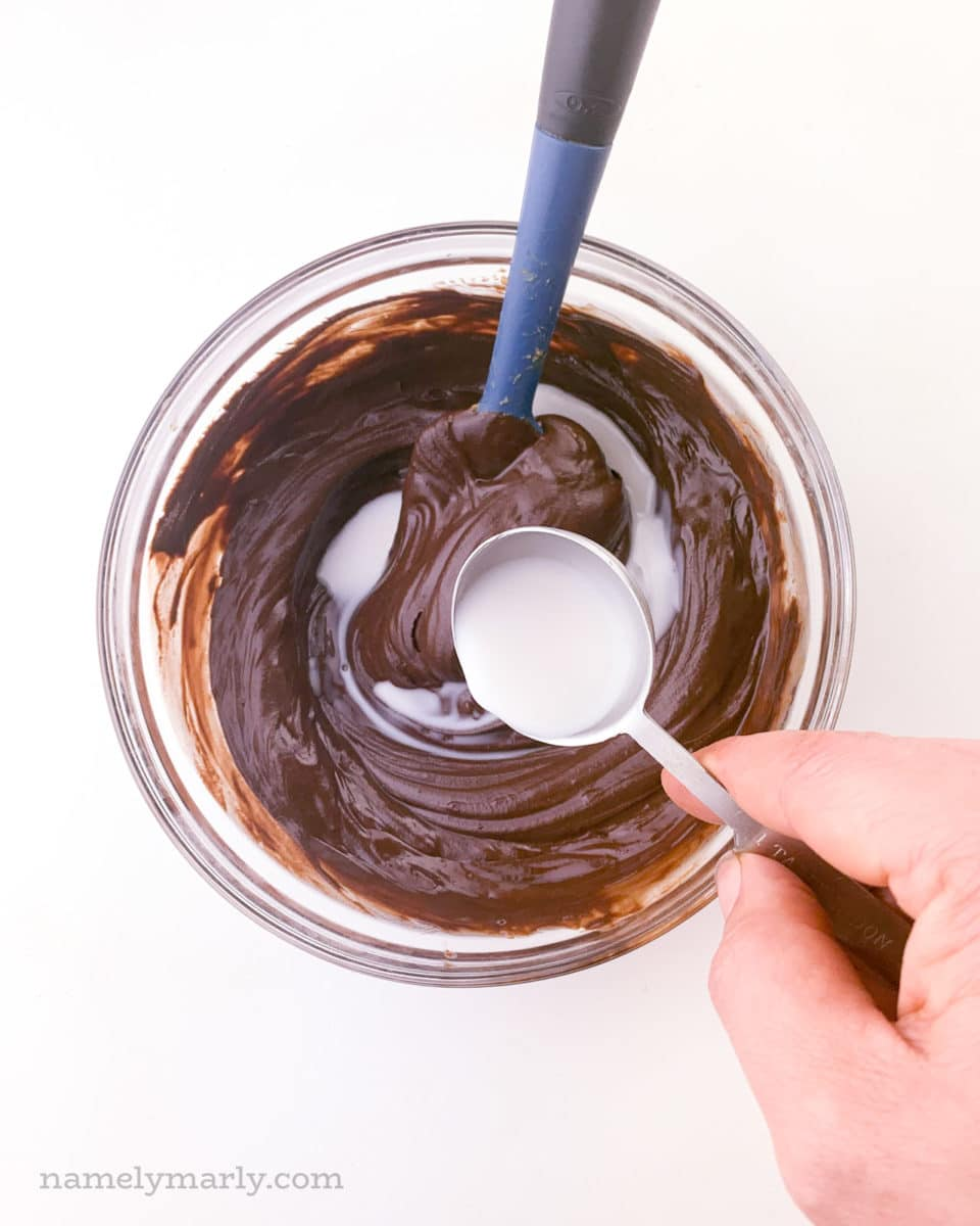 A hand holds a measuring spoon of plant-based milk and is pouring it over melted chocolate.
