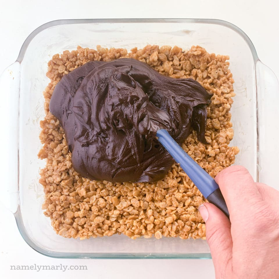 A hand holds a spatula and is spreading soft chocolate ganache over peanut butter rice crispies bars.