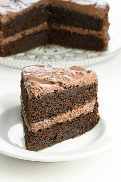 A thick slice of chocolate layer cake on a plate in front of the rest of the cake.