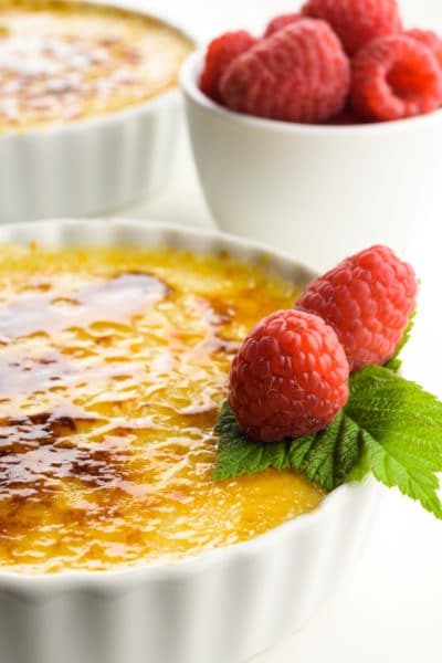 A close up of creme brûlée in white serving dishes with raspberries on top and a bowl of raspberries beside them.