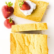 A slice of poundcake has whipped cream and strawberries on it with the rest of the pound cake loaf beside it.