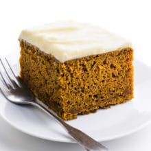 A single slice of vegan pumpkin cake on a plate with a fork beside it.