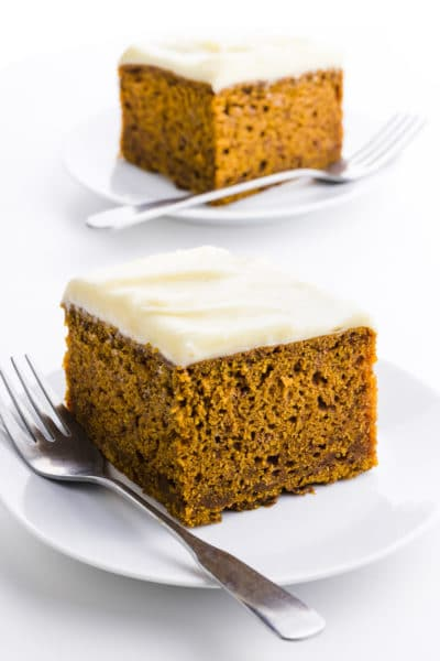 Two slices of pumpkin cake , one in front of the other, with forks beside each slice.