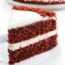 A slice of red velvet cake sits in front of the rest of the cake.