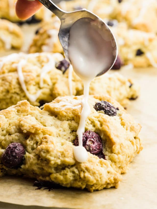 A hand holds a spoon and drizzles frosting over scones.