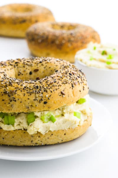A bagel is cut in half and has vegan cream cheese in the middle. There are more bagels behind it with a bowl of more vegan cream cheese.