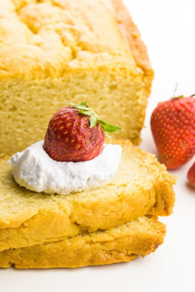 A loaf cake has two slices cut out of it and a dollop of whipped cream is on top with strawberries on top and beside it.