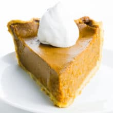 A slice of pumpkin pie with whipped cream sits on a plate.