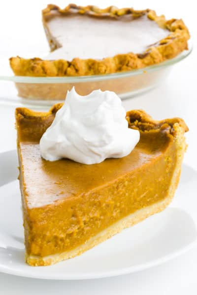 A slice of vegan pumpkin pie with a dollop of whipped cream sits in front of the rest of the pie.