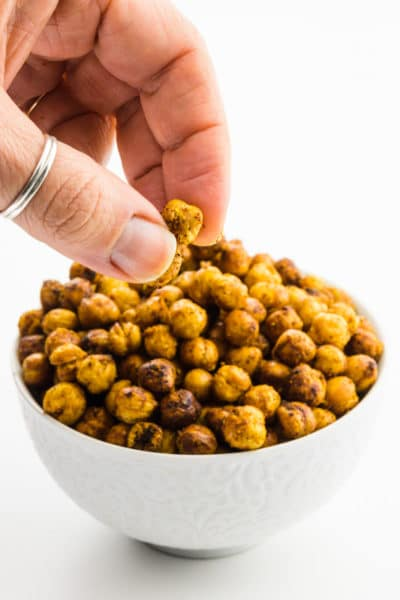A hand reaches in grabs some air fryer chickpeas from a bowl.