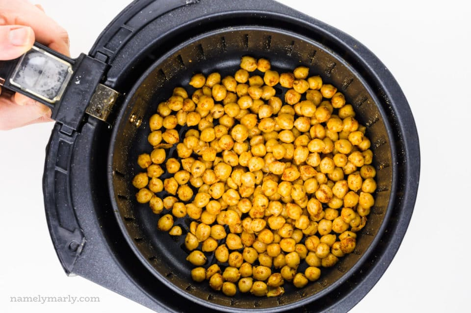 A hand holds an air fryer basket full of spiced chickpeas.