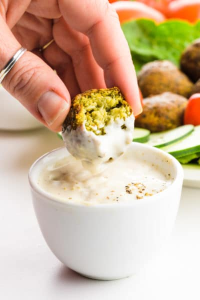 A hand holds an falafel and is dipping it in a white sauce.