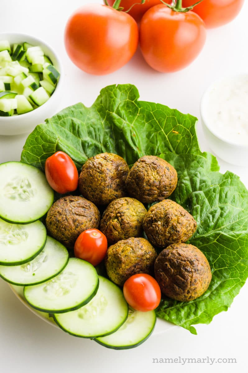 Air Fryer Falafels sit on a plate with veggies, such as lettuce and cucumbers. A bowl of sliced cucumbers is behind it along with a group of tomatoes.