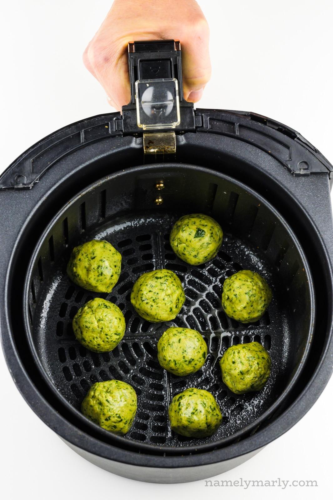 Falafel balls are in an air fryer basket.