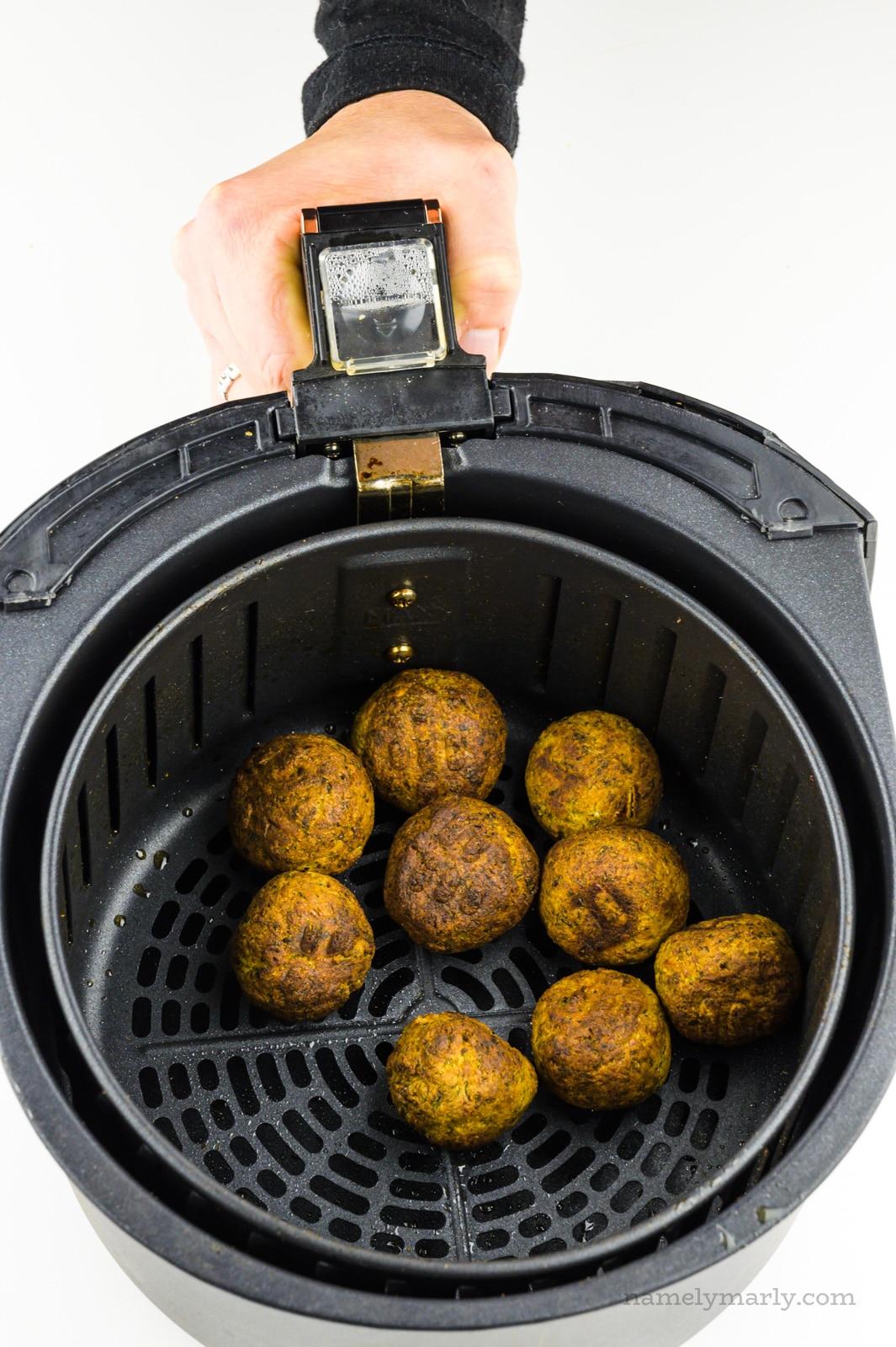 Crispy brown air fried falafel are in an air fryer basket.