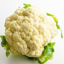 A head of cauliflower with green leaves intact sits on a white counter.