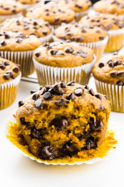 A pumpkin muffin is cut in half with lots of chocolate chips inside and on top. There are several muffins behind it too.