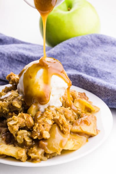 A plate holds vegan apple crisp with ice cream on sauce. Caramel sauce is being poured over the top. A blue napkin and green apple is behind it.