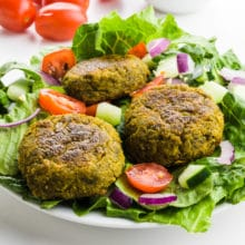 A salad is topped with three falafel patties, with sliced tomatoes, and cucumbers.