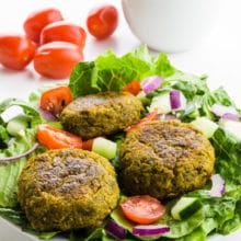 A salad is topped with baked falafel and tomatoes. There are more tomatoes behind it and a bowl full of tahini sauce.