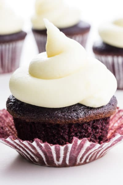 A red velvet cupcake is topped with vegan cream cheese frosting. There are more cupcakes behind it.
